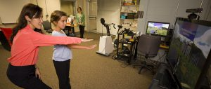 Associate Professor Sun Joo (Grace) Ahn, left, helps nine-year-old Maddie Lacey of Watkinsville, Ga., interact with the virtual buddy fitness kiosk in the Games and Virtual Environments Lab at Grady College, while Maddie's mother, Cara Lacey, looks on.