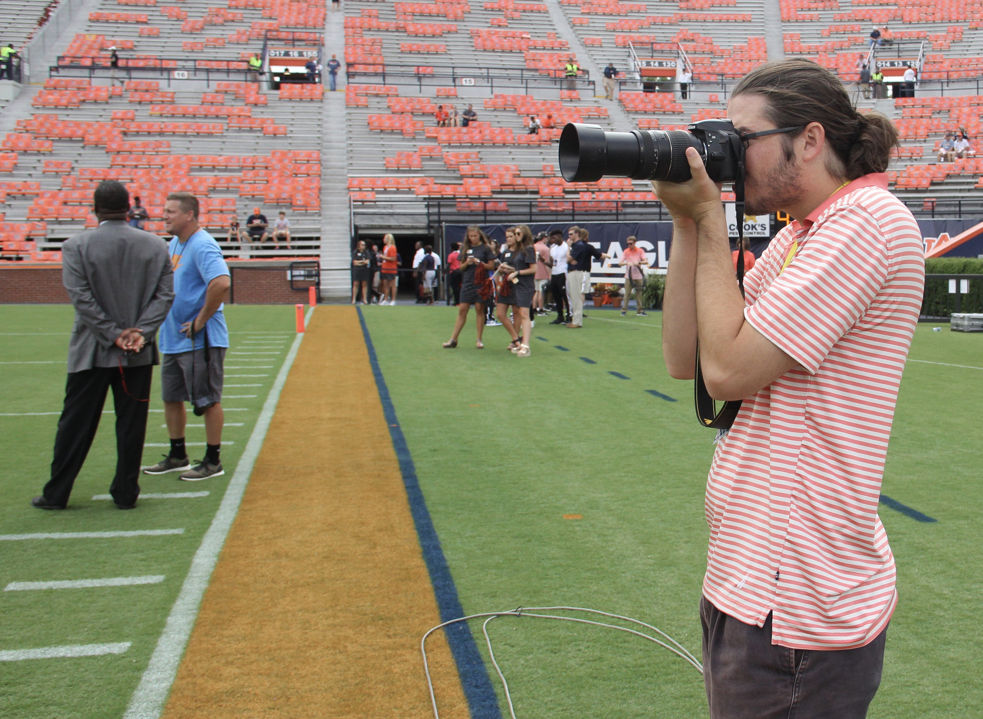 Wolk incorporates several tools of the trade when covering college football including photography and Facebook Live.