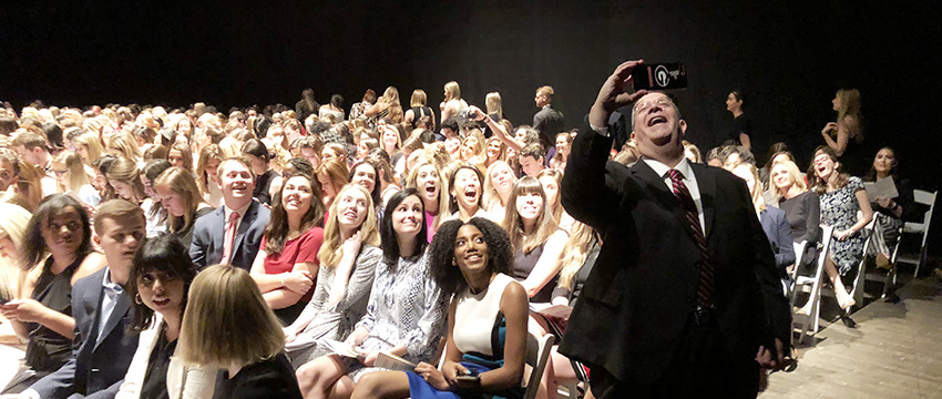 Dean Charles Davis takes a selfie with Grady students backstage moments prior to curtain opening on the Spring 2018 Grady Convocation