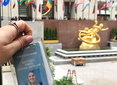 Brittany Paris holding her Dateline NBC internship badge in Rockefeller Center.