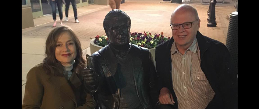 2017 Academy Award nominee Isabelle Huppert is pictured with a statue of Roger Ebert giving his famous 'thumbs-up' and Eberfest Director Nate Kohn.