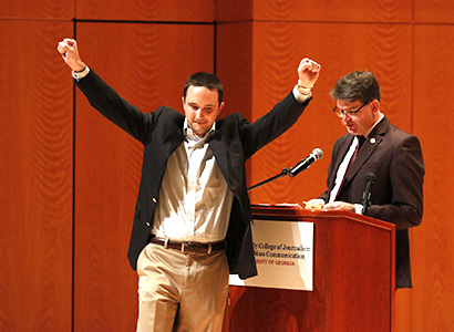 A student celebrates with a moment of victory as he crosses the stage at the Grady College Convocation ceremonies.