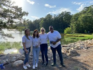 Drake and the other interns standing in front of a lake in white t-shirts under blue sunny skies